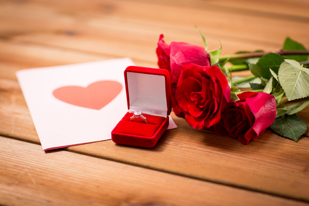 flirtation: love, proposal, valentines day and holidays concept - close up of gift box with diamond engagement ring, red roses and greeting card on wood Stock Photo