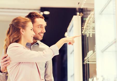 verlobung: Verkauf, Konsum und Menschen Konzept - glückliches Paar zeigt mit dem Finger auf Schaufenster an Juweliergeschäft im Einkaufszentrum