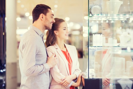 store man: sale, consumerism and people concept - happy couple pointing finger to shopping window at jewelry store in mall