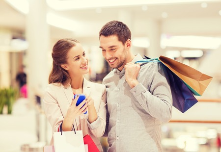 la vendita, il consumismo, la tecnologia e le persone concetto - giovane coppia felice con le borse della spesa e smartphone parlando in centro commerciale
