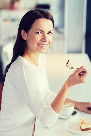 woman eating cake: leisure, drinks, people and lifestyle concept - smiling young woman eating cake and drinking coffee at cafe Stock Photo