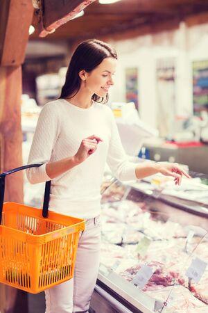 venta, las compras, el consumismo y la gente concepto - mujer joven feliz con la cesta de alimentos en el mercado