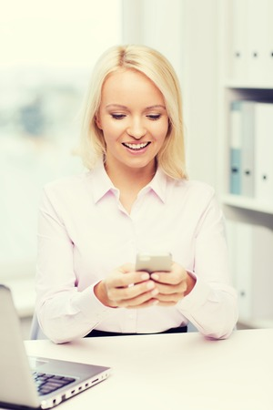 chatty: education, business, communication and technology concept - smiling businesswoman or student with smartphone texting message in office