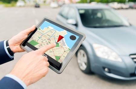 交通、ビジネス旅行、ナビゲーション、技術と人のコンセプト - タブレット pc コンピューターと屋外の車の gps ナビゲーターと男性の手のクローズ