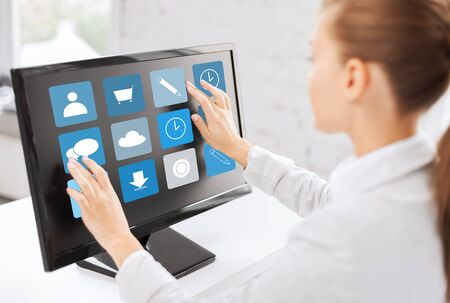 touch screen: business, people, technology and media concept - woman with application icons on computer touchscreen in office
