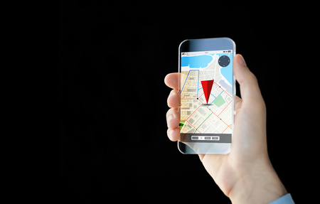 mobile app: people, modern technology, application and navigation concept - close up of male hand holding and showing transparent smartphone with gps and road map on screen over black background Stock Photo