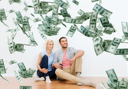 budget repair: home, people, moving, finances and real estate concept - happy couple of man and woman sitting on floor and dreaming at new place over dollar money falling from above