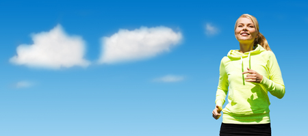 sport, fitness, exercising, people and lifestyle concept - female runner jogging over blue sky and clouds background