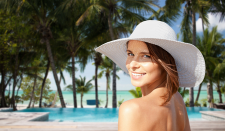sunhat: summer holidays, travel, people, tourism and vacation concept - happy young woman in sunhat on beach over swimming pool and palm trees at hotel resort background