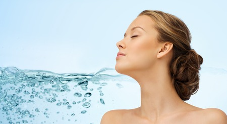 fresh concept: beauty, people, moisturizing, skin care and health concept - young woman face with closed eyes and shoulders over water splash background