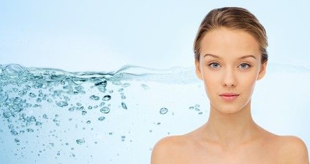 beauty, people, moisturizing, body care and health concept - smiling young woman face with shoulders over water splash background