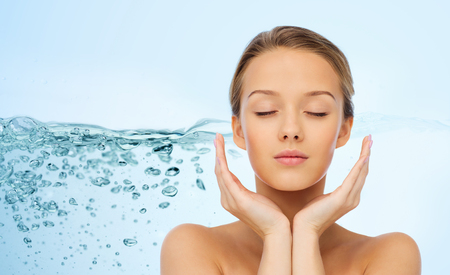 beauty, people, moisturizing, skin care and health concept - young woman face and hands over water splash background 스톡 콘텐츠