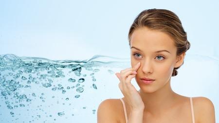 아름다움, 사람들, 화장품, 보습 및 피부 관리 개념 - 워터 스플래쉬 배경 위에 그녀의 얼굴에 크림을 적용 젊은 여자