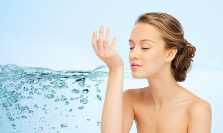 fragrant scents: beauty, aroma, people and body care concept - young woman smelling perfume from wrist of her hand over water splash background Stock Photo