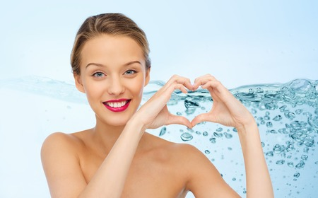 beauty, people, love, valentines day and make up concept - smiling young woman with pink lipstick on lips showing heart shape hand sign over water splash background
