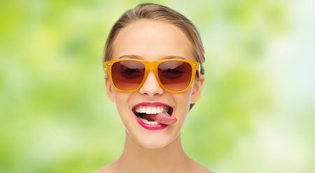 young woman smiling: people, expression, joy and fashion concept - smiling young woman in sunglasses with pink lipstick on lips showing tongue over green summer background