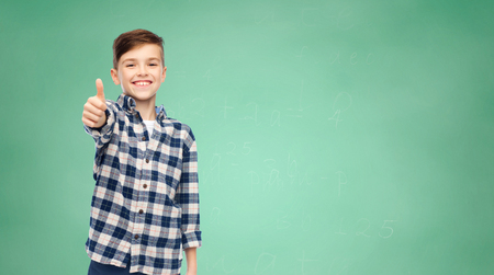 school board: gesture, childhood, school, education and people concept - smiling student boy in checkered shirt and jeans showing thumbs up over green school chalk board background