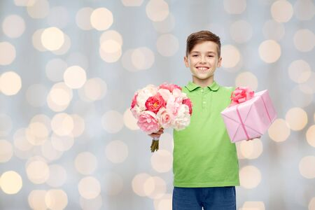 pre teen boy: childhood, holidays, presents and people concept - happy boy holding flower bunch and gift box over lights background