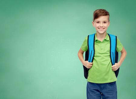 kinderjaren, school, onderwijs en mensenconcept - gelukkige glimlachende studentenjongen met schooltas over de groene achtergrond van het schoolbord