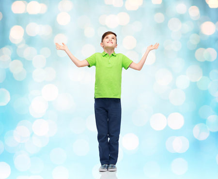 gladness: childhood, achievement, gladness and people concept - happy smiling boy in green polo t-shirt raising hands and looking up over blue holidays lights background