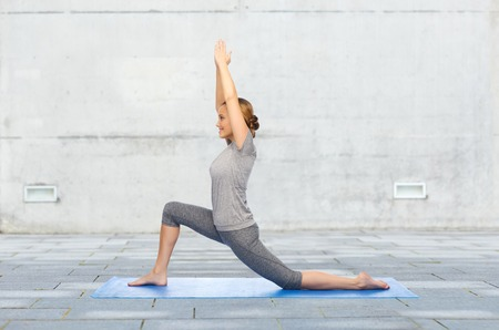 lunge: fitness, sport, people and healthy lifestyle concept - happy woman making yoga in low lunge pose on mat over urban street background Stock Photo