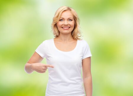 woman white shirt: gesture, advertisement and people concept - smiling middle aged woman in blank white t-shirt pointing finger to herself over green natural background