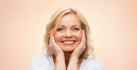 middle age woman: beauty, people and skincare concept - smiling middle aged woman in white shirt touching face over beige background Stock Photo