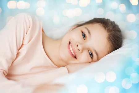 wellness sleepy: people, children, rest and comfort concept - happy smiling girl lying awake in bed over blue lights background Stock Photo
