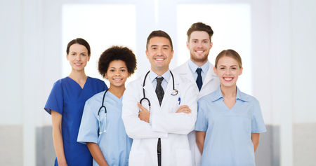 profession: hospital, profession, people and medicine concept - international group of happy doctors at hospital