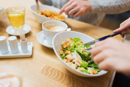 eating salad: people, leisure and food concept - close up friends having dinner and eating at restaurant