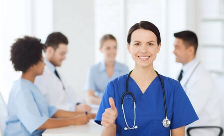 medics: clinic, profession, people and medicine concept - happy female doctor over group of medics meeting at hospital showing thumbs up gesture