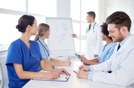 health education: medical education, health care, medical education, people and medicine concept - group of happy doctors or interns with mentor meeting and drawing on flip board on presentation at hospital Stock Photo