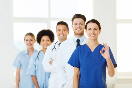 medical education: hospital, profession, gesture, people and medicine concept - group of happy doctors showing ok hand sign at hospital