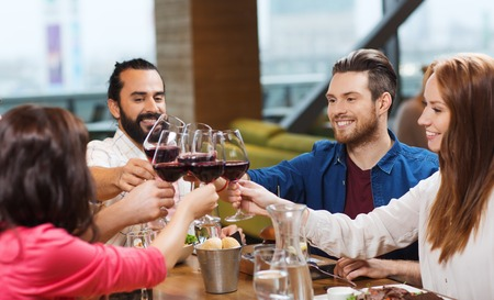 Ocio, celebración, comida y bebida, la gente y el concepto de vacaciones - sonriendo amigos cenando y bebiendo vino tinto en el restaurante Foto de archivo - 52680908