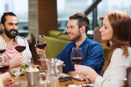 food and wine: leisure, food and drinks, celebration people and holidays concept - smiling friends having dinner and drinking red wine at restaurant