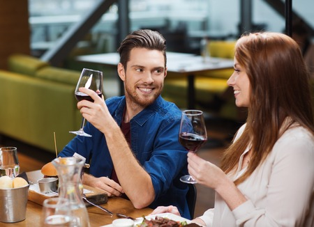tomando vino: leisure, eating, food and drinks, people and holidays concept - smiling couple having dinner and drinking red wine at restaurant Foto de archivo