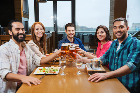 family and friends: leisure, eating, food and drinks, people and holidays concept - smiling friends having dinner and drinking beer at restaurant or pub