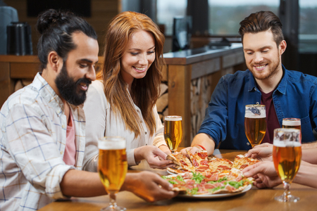 leisure, food and drinks, people and holidays concept - smiling friends eating pizza and drinking beer at restaurant or pub Archivio Fotografico