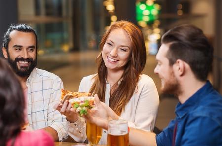 Freizeit, Essen und Getränke, die Menschen und Ferien-Konzept - lächelnde Freunde Pizza und Bier trinken im Restaurant oder Pub Essen