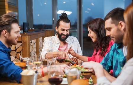 family and friends: leisure, eating, food, people and holidays concept - smiling friends having dinner and tasting each other dish at restaurant