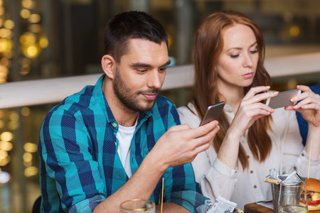 eating dinner: leisure, technology, lifestyle and people concept - couple with smartphones dining at restaurant Stock Photo