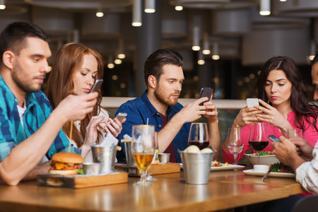 leisure, technology, lifestyle and people concept - friends with smartphones dining at restaurant Foto de archivo