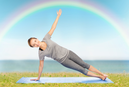 fitness, sport, people and healthy lifestyle concept - woman making yoga in side plank pose on mat over blue sky, rainbow and sea background