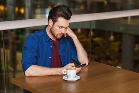 persona triste: ocio, tecnología, estilo de vida y las personas concepto - hombre con el teléfono inteligente y el café en el restaurante Foto de archivo