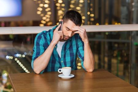 hombres jovenes: ocio, tecnología, estilo de vida y las personas concepto - hombre con el teléfono inteligente y el café en el restaurante Foto de archivo