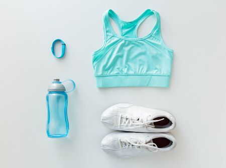 set up: sport, fitness, healthy lifestyle, cardio training and objects concept - close up of female sports clothing, heart-rate watch and bottle set