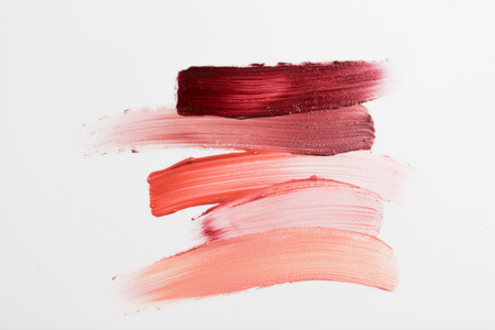 to smear: cosmetics, makeup and beauty concept - close up of lipstick smear sample