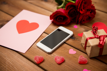 attentions: romance, valentines day and holidays concept - close up of smartphone, gift box, red roses and greeting card with heart-shaped candies on wood