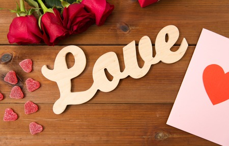 uprzejmości: romance, valentines day and holidays concept - close up of word love, gift box, red roses and greeting card with heart-shaped candies on wood Zdjęcie Seryjne