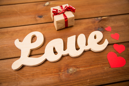 courtship: love, date, romance, valentines day and holidays concept - close up of word love with gift box and red hearts on wood